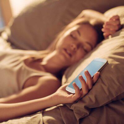 Frau mit Handy im Bett ohne Nightholder