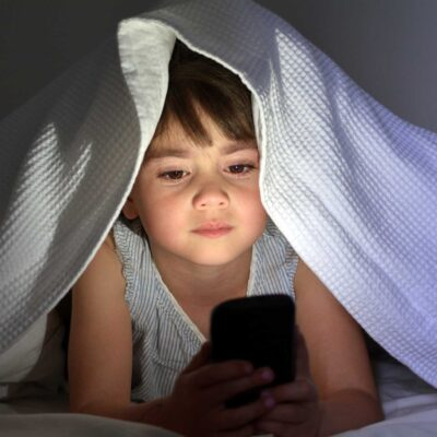 Kind mit Handy im Bett